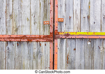 Old gray gate on large rusty hinges