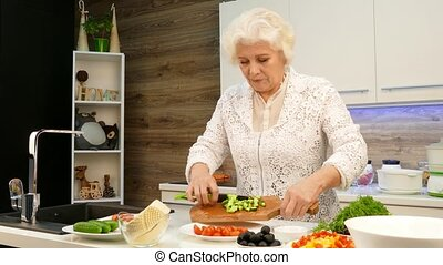 Old gray-haired woman cut cucumbers in the kitchen.