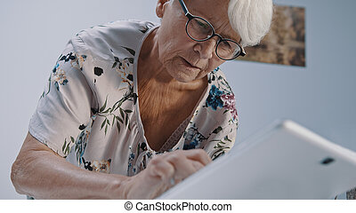 Old gray haired woman with eyegalsses using the tabet. Low angle shot