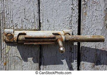 gray metal latch on a wooden plank door