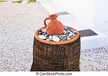 Old Greek clay jug on stones on the street