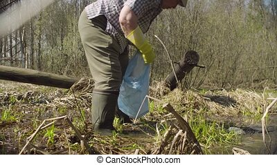 Old green activist collecting trash in the forest pond -...