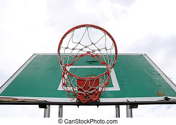Old green board of basketball with red hoop and white-red mesh on the white sky background.