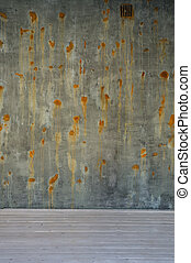 old green brown surface and concrete wall with rusted spots on white wooden floor