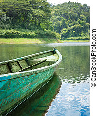 Old green iron boat in lake.