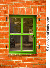 old green window in a red brick wall