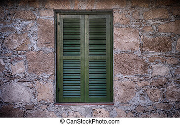 Old green window with closed shutters