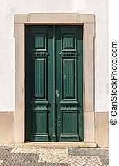 Old green wooden door in house facade