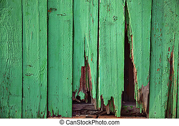 old green wooden wall with a hole.