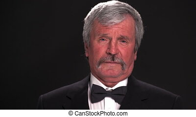 Old grey haired man in an expensive tuxedo looking at the camera in a dark room isolated on a black background. Prores 422