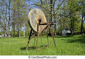 Old grindstone in yard - Old grindstone sits in an abandoned...