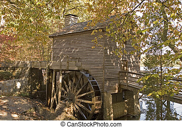 Old Grist Mill - An old wooden grist mill in the woods by a...