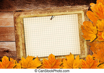Old grunge paper with autumn leaves on the wooden background