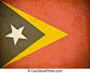 old grunge paper with East Timor flag background