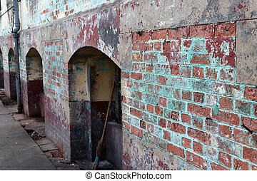 Old grungy brick wall with arched door.