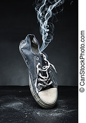 Old gym-shoe in smoke - Old gym-shoe from which the smoke...