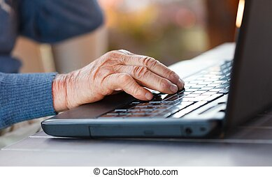 Old hand on a laptop - Closeup of an old man using the...