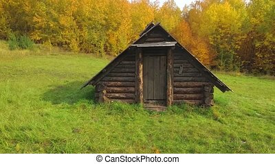 Old, handmade log cabin, standing in ramshackle condition, in an agricultural field in Rural Ukraine. FullHD 1080p video