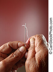 Old hands and needle