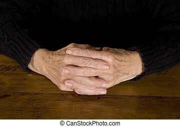 old hands resting at the wooden table
