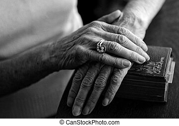 Old Hands - Old Woman\\\'s Hands on Her Bible Wearing Her...
