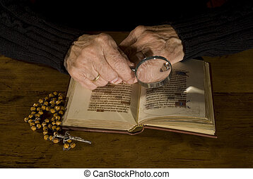 Old hands with bible and rosary - old person is reading and ...