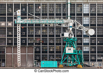 Old harbor crane in front of an ancient factory