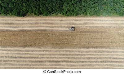 Old harvester reaps wheat. Aerial