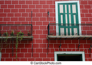 Detail of Old Havana typical facade with balcony and red bricks
