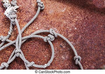 Old Hemp rope on rusty metal background,