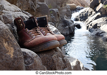 Old hiking boots in front of waterfall