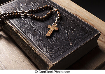 Old holy bible with rosary