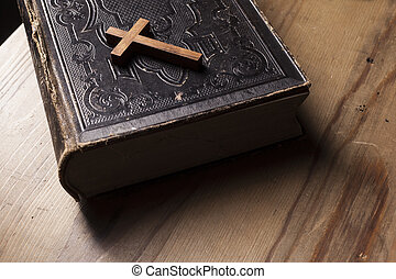 Old holy bible with wooden Christian cross