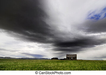 Old Homestead in Field - Old cabin in field with storm...