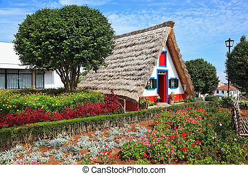 Charming white cottage with a thatched roof gable