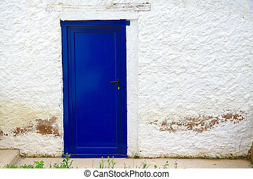 Old house white wall with new blue door