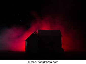 Old house with a Ghost in the moonlit night or Abandoned Haunted Horror House in fog. Old mystic villa with surreal big full moon. Horror Halloween concept.