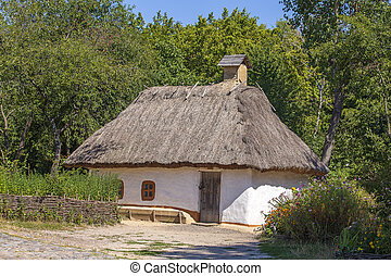 Old house with a thatched roof in Ukraine. Ancient traditional ukrainian house with a straw roof