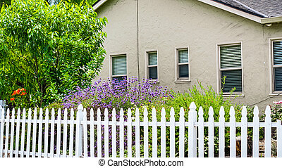 Old house with flowering garden and picket fence in Mountain View, San Francisco bay area, California