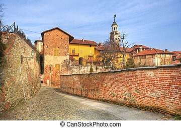 Old houses and paved street in Saluzzo, Italy.