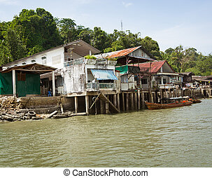 Old houses on river bank. Thailand