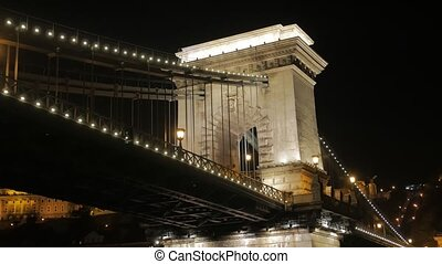 Old illuminated bridge at night Szechenyi Chain Bridge Budapest Hungary view from the river Danube tracking camera movement closeup