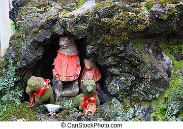 Old inari fox statue in shinto shrine