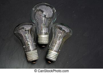 Old incandescent light bulb on dark background.