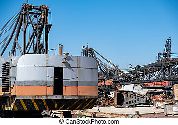 Old industrial ship boat in dry dock for repair, harbor in Greece, sunny day.