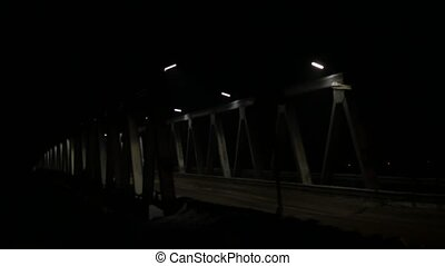 old iron bridge with car traffic at evening. headlights...