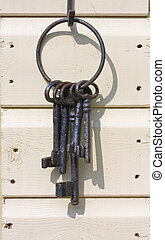 Old iron keys on a wooden shed wall