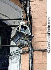 Old iron lantern with a light bulb hanging on the wall