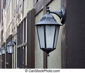 Old iron street lantern on wooden wall