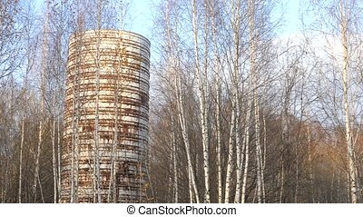 Old iron water tower. Abandoned building in the forest
